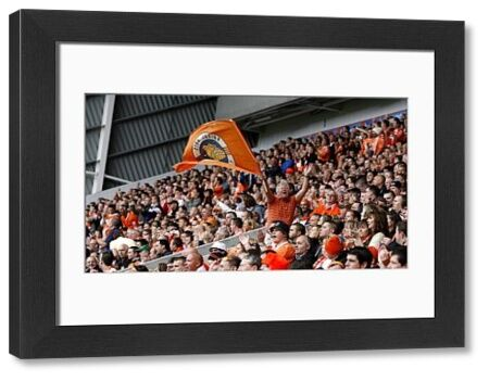 A Blackpool fan waves a flag in the stands