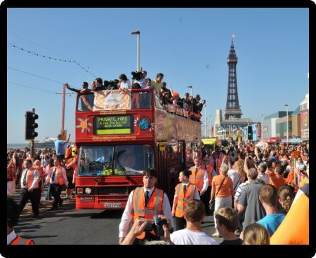 The open top bus carrying the Blackpool players makes it's way down the promenade in Blackpool, Lancashire