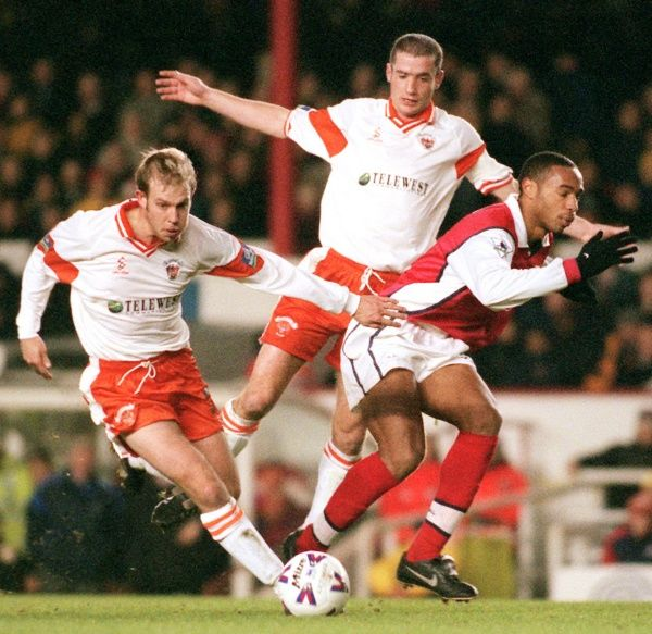 Arsenal's Thierry Henry (right) is hustled off the ball by Blackpool's John Hills (left)