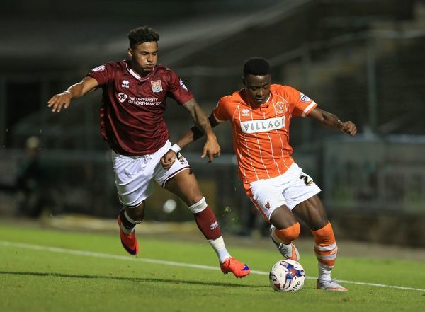 Northampton Town's Josh Lelan (left) and Blackpool's Bright Osayi-Samuel battle for the ball