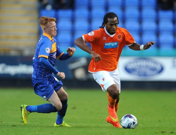 Shrewsbury Town's Ryan Woods (left) and Blackpool's Nathan Delfouneso battle for the ball