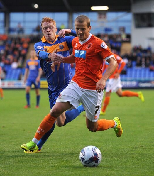 Shrewsbury Town's Ryan Woods (left) and Blackpool's Tomasz Cywka (right) battle for the ball