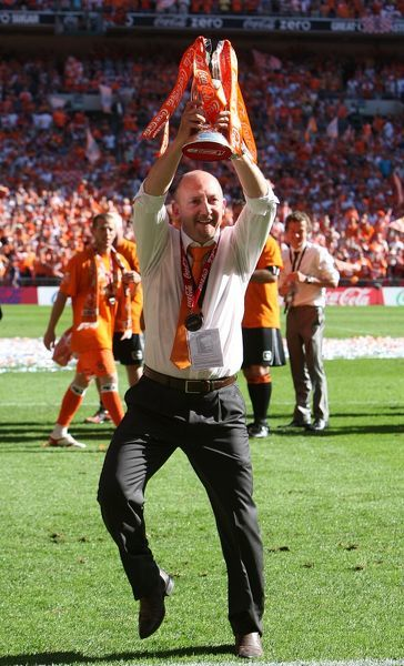 Blackpool manager Ian Holloway celebrates with the trophy after the final whistle