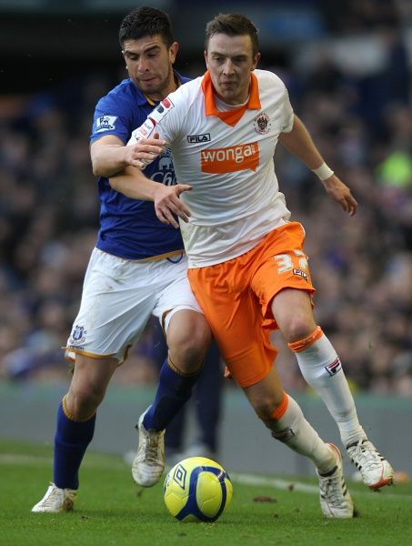 Everton's Denis Stracqualursi (left) and Blackpool's Danny Wilson (right) in action