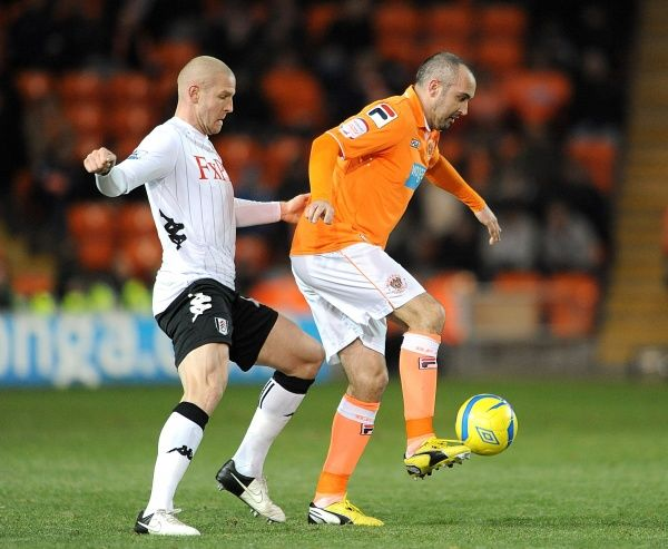 Fulham's Philippe Senderos (left) and Blackpool's Gary Taylor-Fletcher (right) battle for the ball