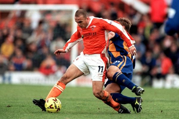 Blackpool's Lee Collins (l) holds off Shrewsbury Town's Nigel Jemson (r)