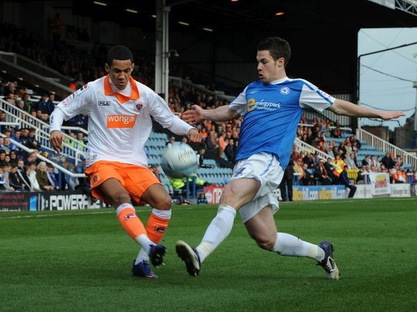 Peterborough United's Tommy Rowe and Blackpool's Thomas Ince battle for the ball