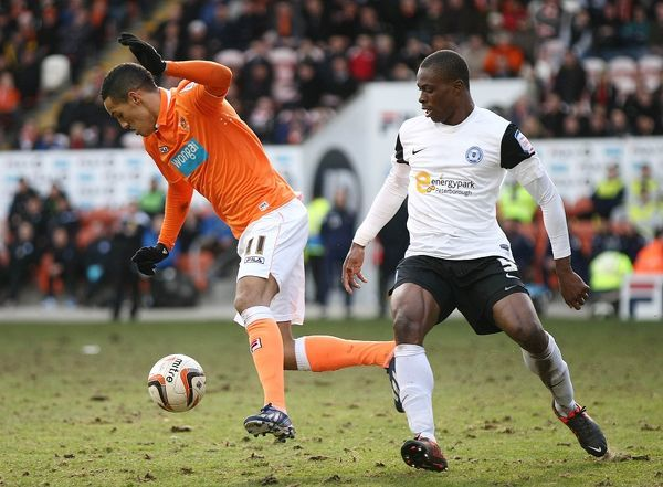 Blackpool's Tom Ince (left) and Peterborough United's Gabriel Zakuani (right) in action