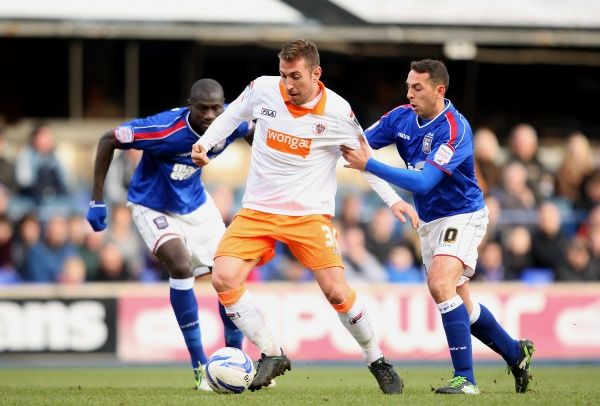 Blackpool's Angel Martinez (centre) in action with Ipwich's Michael Chopra (right)
