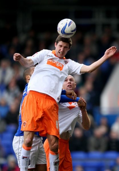Blackpool's Chris Basham gets to the ball first in the air