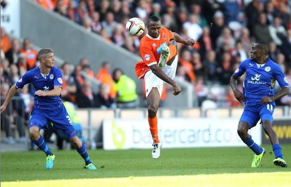 Blackpool's Ricardo Fuller takes Leicester City's Paul Konchesky and Lloyd Dyer