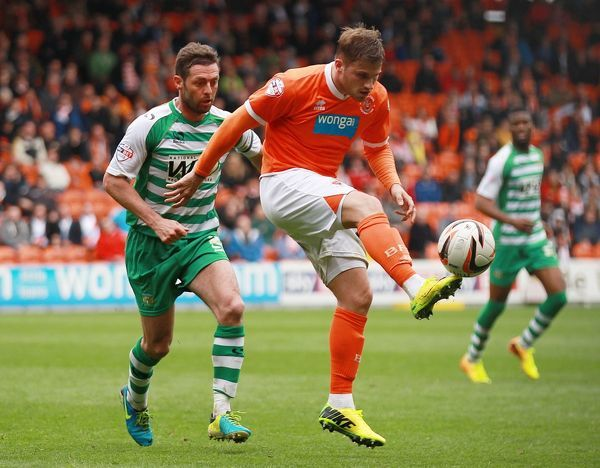 Blackpool's David Goodwillie and Yeovil Town's Jamie McAllister in action