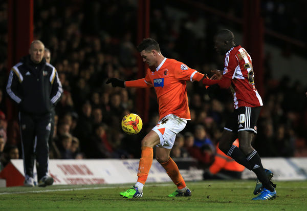 Blackpool's Gary Madine, (left) battles for the ball with Brentford's Toumani Diagouraga, (right)