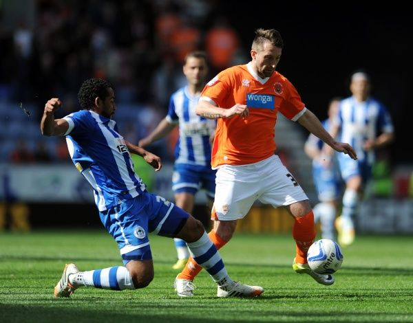 Wigan Athletics's Jean Beausejour (Left) tackles Blackpool's Stephen Dobbie
