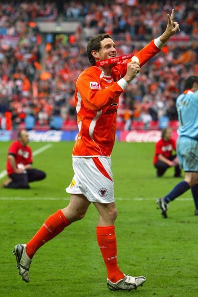 Blackpool's Scott Vernon celebrates promotion with his winner's medal after the game