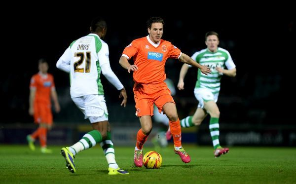 Blackpool's Dan Gosling (centre) runs at Yeovil Town's Liam Davis (left)